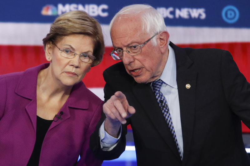 Democratic presidential candidates, Sen. Elizabeth Warren, D-Mass., left, and Sen. Bernie Sanders, I-Vt., talk during a Democratic presidential primary debate Wednesday, Feb. 19, 2020, in Las Vegas, hosted by NBC News and MSNBC. (AP Photo/John Locher)