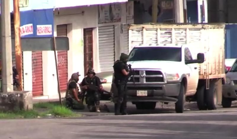 """In this AFPTV screen grab armed gunmen take position in a street of Culiacan, capital of jailed kingpin Joaquin """"El Chapo"""" Guzman's home state of Sinaloa, on October 17, 2019. - Heavily armed gunmen in four-by-four trucks fought an intense battle against Mexican security forces Thursday in the city of Culiacan, capital of jailed kingpin Joaquin """"El Chapo"""" Guzman's home state of Sinaloa. (Photo by STR / AFP) (Photo by STR/AFP via Getty Images)"""