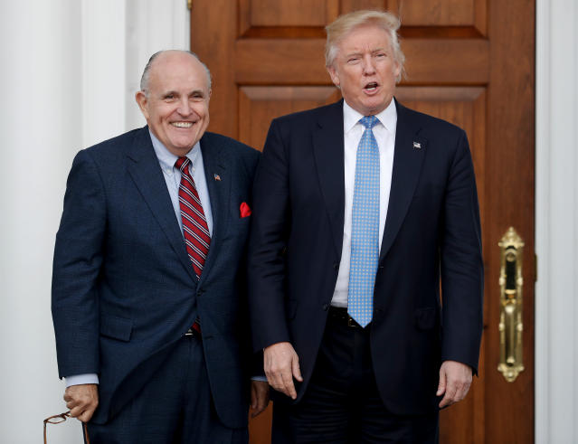 Donald Trump, right, and former New York Mayor Rudy Giuliani pose for photographs as Giuliani arrives at the Trump National Golf Club Bedminster clubhouse in Bedminster, N.J. Giuliani is joining the legal team defending President Donald Trump in the special counsel's Russia investigation. That's according to a statement from Trump personal attorney Jay Sekulow. (AP Photo/Carolyn Kaster)