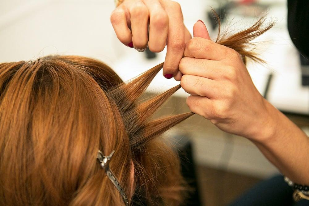 <p>Starting with a section of hair from behind one ear, separate it into three strands.</p>