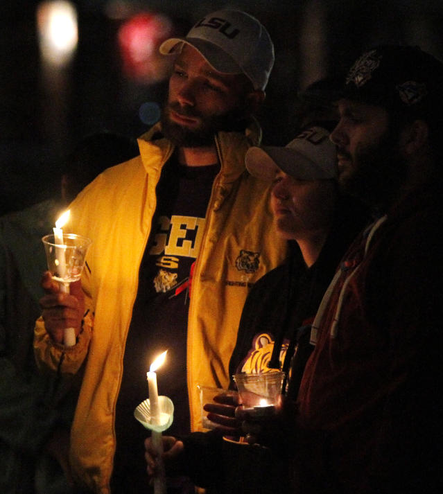 James Stephens, left, and Autumn, center, join others to pray for a 5-year-old boy taken hostage, in Midland City, Ala., Sunday, Feb. 3, 2013. Authorities say Jim Lee Dykes, 65 — a decorated Vietnam-era veteran known as Jimmy to neighbors — gunned down a school bus driver and then abducted a 5-year-old boy from the bus, taking him to an underground bunker on his rural property. The driver, 66-year-old Charles Albert Poland Jr., who was shot trying to protect children on his bus, was buried Sunday. (AP Photo/Butch Dill)