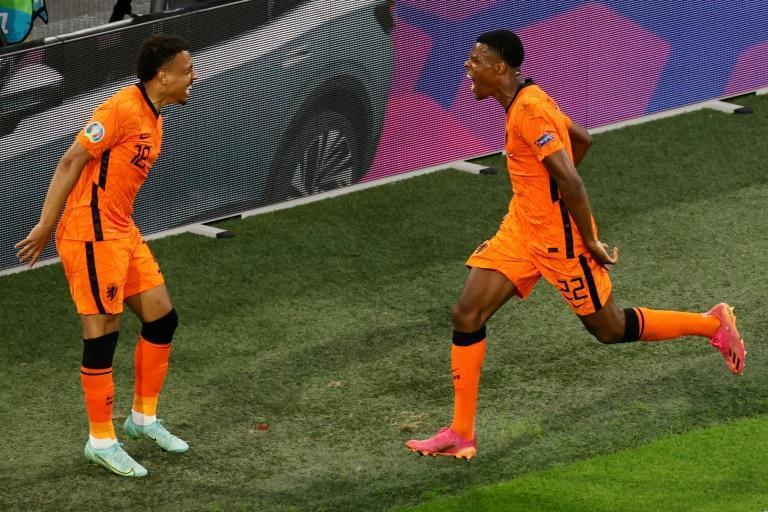 Denzel Dumfries (R) celebrates with Donyell Malen after scoring the Netherlands' second goal