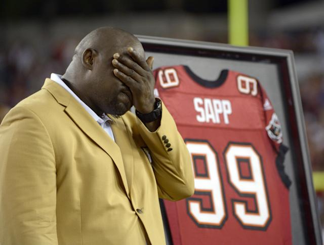 Former Tampa Bay Buccaneers player Warren Sapp wipes his face after being inducted in the Ring of Honor ceremony during halftime in an NFL football game between the Tampa Bay Buccaneers and the Miami Dolphins in Tampa, Fla., Monday, Nov. 11, 2013.(AP Photo/Phelan M. Ebenhack)