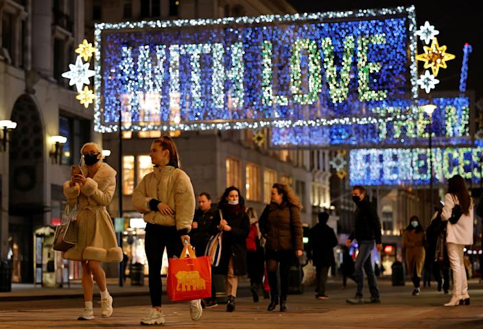Pedestrians, some wearing face masks or coverings due to the COVID-19 pandemic, walk past Christmas lights on Oxford Street in central London on November 17, 2020. - Britain has been the worst-hit nation in Europe recording more than 50,000 coronavirus deaths from some 1.2 million positive cases. (Photo by Tolga Akmen / AFP) (Photo by TOLGA AKMEN/AFP via Getty Images)