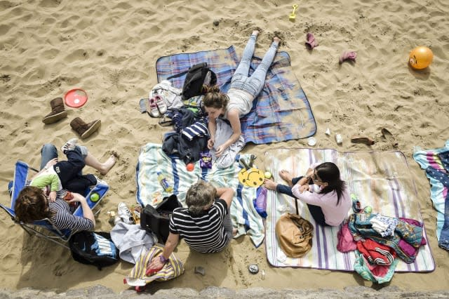 People enjoy the beach at Barry Island, in Wales, as most of England and Wales will enjoy sunshine and warm conditions over the next three days as forecasters predict temperatures could reach as high as 24C (75.2F) in London on Wednesday - 10C (50F) above the average for the time of year. PRESS ASSOCIATION Photo. Picture date: Monday April, 13, 2015. See PA story WEATHER Spring. Photo credit should read: Ben Birchall/PA Wire
