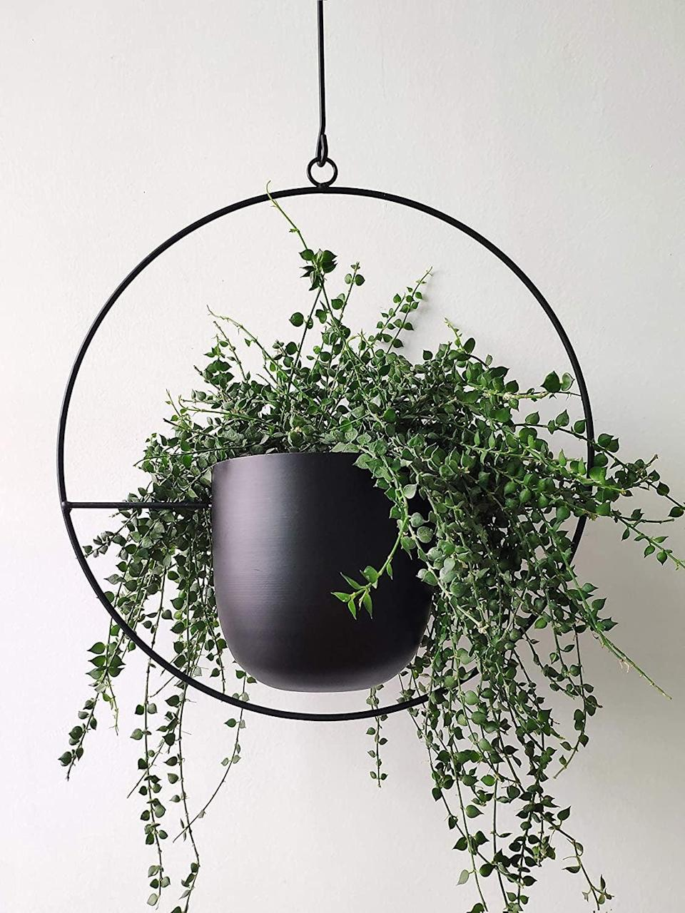<p>If you love plants but don't have enough room to store them all indoors, you need to get your hands on a few of these <span>Riseon Boho Black Metal Plant Hanger</span> ($33). The minimalist plant hanger can be wall mounted or even hung from the ceiling for a whimsical look.</p>