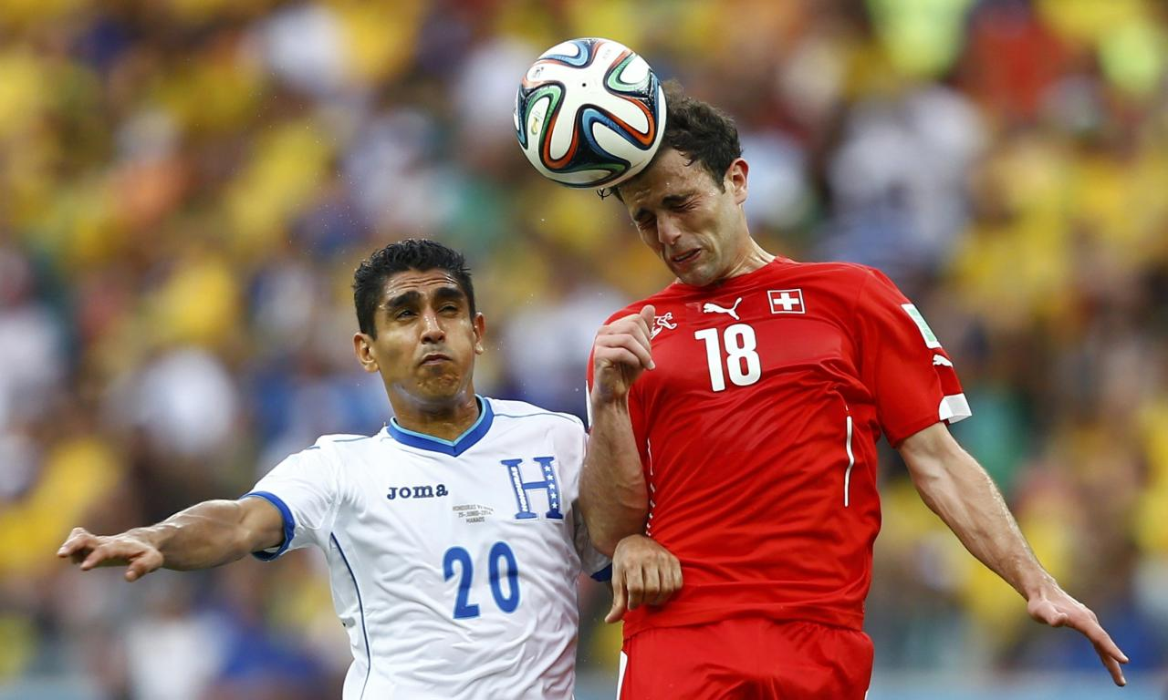 Switzerland's Admir Mehmedi (R) fights for the ball with Jorge Claros of Honduras during their 2014 World Cup Group E soccer match at the Amazonia arena in Manaus June 25, 2014. REUTERS/Dominic Ebenbichler (BRAZIL - Tags: SOCCER SPORT WORLD CUP)