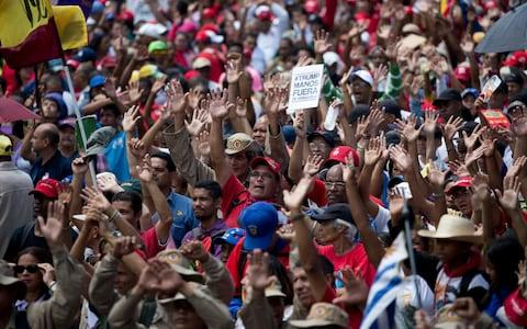 """Supporters of Venezuela's President Nicolas Maduro take part in an """"anti-intervention"""" march earlier this week - Credit: Ariana Cubillos/AP"""