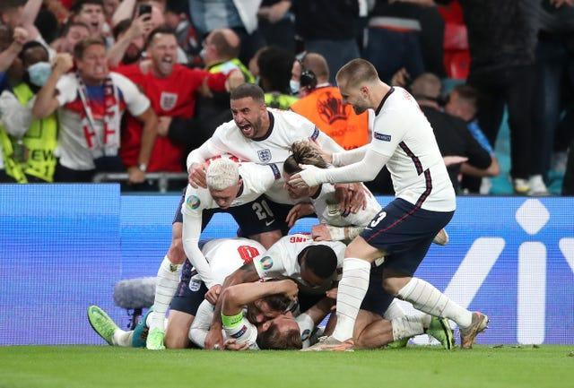 Harry Kane is mobbed by team-mates after firing England ahead from the penalty spot