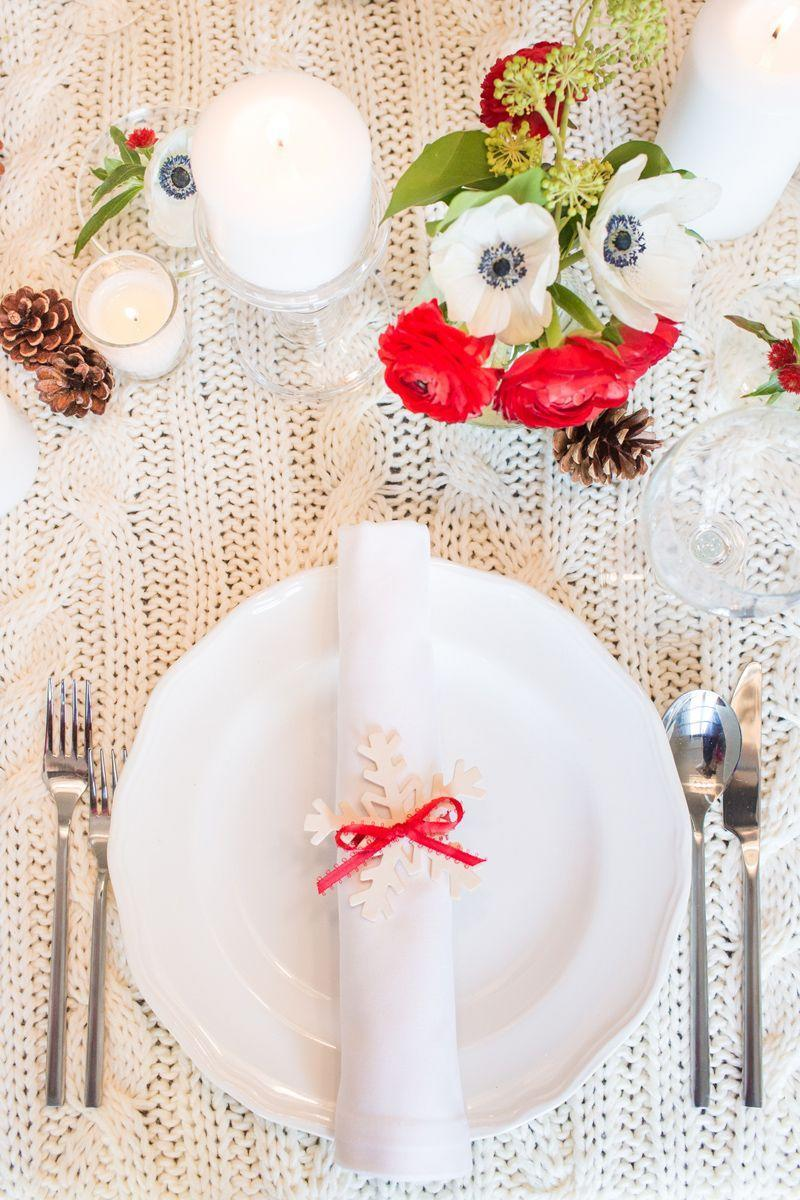 """<p>On top of a knit tablecloth, holiday favorites like pine cones and flowers look a little less traditional. Top off each place setting with a DIY <a href=""""https://www.goodhousekeeping.com/holidays/christmas-ideas/how-to/g46/snowflake-napkin-ring/"""" rel=""""nofollow noopener"""" target=""""_blank"""" data-ylk=""""slk:snowflake napkin ring"""" class=""""link rapid-noclick-resp"""">snowflake napkin ring</a>.</p><p><a class=""""link rapid-noclick-resp"""" href=""""https://www.amazon.com/Christmas-Assorted-Snowflake-Embellishment-Ornament/dp/B01IUGHGN4?tag=syn-yahoo-20&ascsubtag=%5Bartid%7C10055.g.2196%5Bsrc%7Cyahoo-us"""" rel=""""nofollow noopener"""" target=""""_blank"""" data-ylk=""""slk:SHOP WOODEN SNOWFLAKES"""">SHOP WOODEN SNOWFLAKES</a></p>"""