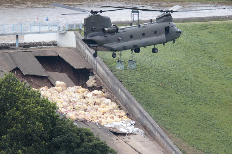 "An RAF Chinook helicopter drops aggregate to help shore up a reservoir at risk of collapse, threatening to engulf the town of Whaley Bridge in the Peak District, England, Friday, Aug. 2, 2019. A British military helicopter has dropped sandbags to shore up a reservoir wall as emergency services worked frantically to prevent a rain-damaged dam from collapsing. Engineers say they remain ""very concerned"" about the integrity of the 19th-century Toddbrook Reservoir, which contains around 1.3 million metric tons (1.5 million (U.S tons) of water. (AP Photo/Jon Super)"