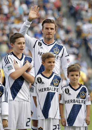 Los Angeles Galaxy's David Beckham, top center, of England, waves as he stands with his sons, from left, Brooklyn, Romeo and Cruz before the MLS Cup championship soccer match against the Houston Dynamo in Carson, Calif., Saturday, Dec. 1, 2012. (AP Photo/Jae C. Hong)