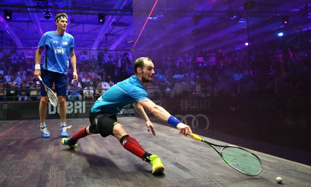 Gregory Gaultier (front) plays a backhand to Cameron Pilley in the men's final match of the Dubai PSA World Series finals squash tournament, on May 28, 2016 (AFP Photo/Marwan Naamani)