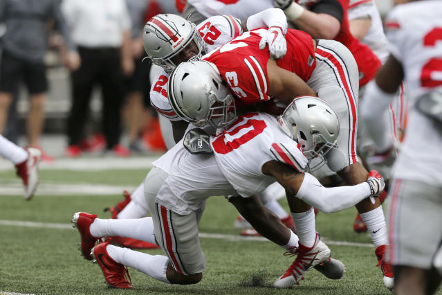 Ohio State running back Master Teague (33) is tackled by safety Jahsen Wint and cornerback Amir Riep during their NCAA college spring football game Saturday, April 14, 2018, in Columbus, Ohio. (AP Photo/Jay LaPrete)