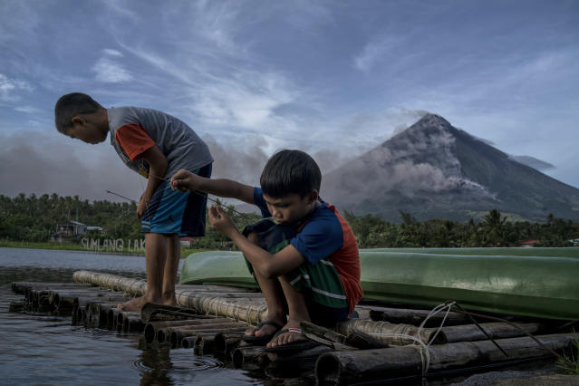 <p>Children fish as Mayon volcano spews ash and lava on January 17, 2018 in Camalig, Albay, Philippines. (Photo: Jes Aznar/Getty Images) </p>