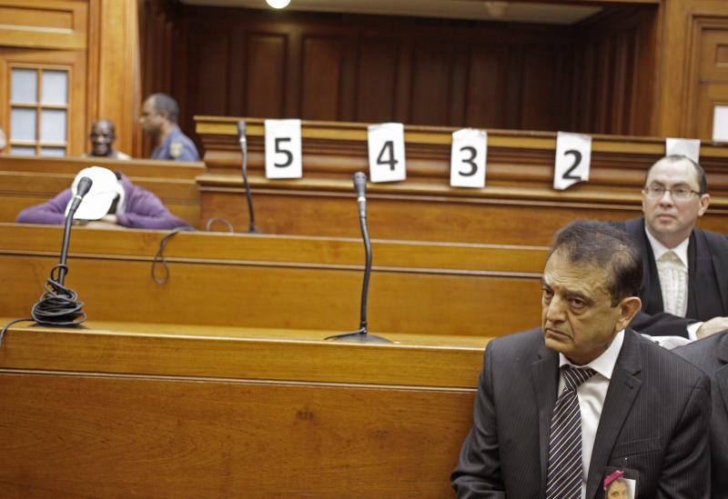 "Vinod Hindocha, right, the father of slain bride Anni Dewani stands in court at Cape Town, South Africa, Wednesday, Dec. 5, 2012. A South African judge sentenced the triggerman in the 2010 honeymoon slaying of a Swedish bride to life in prison Wednesday, calling the shooter ""a merciless and evil person"" who deserved the maximum punishment for his crime. Prosecutors say the newlywed's British husband orchestrated the November 2010 killing. Judge Robert Henney did not hold back his contempt while sentencing Xolile Mngeni, seen at left in white hat, for the killing of 28-year-old Anni Dewani. Henney said that the shooter showed no remorse. (AP Photo/Schalk van Zuydam)"