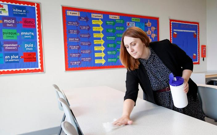 Principal Cara Ackroyd cleans a classroom desk at Outwood Academy Shafton in Barnsley, South Yorkshire, as preparations are made before the start of the new term - Danny Lawson/ PA