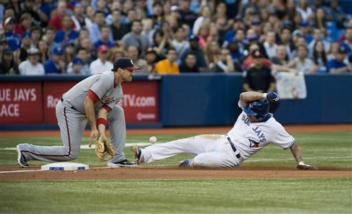 Toronto Blue Jays' Brett Lawrie pushes to third base against Washington Nationals' Ryan Zimmerman on a single by Colby Rasmus during the third inning of an interleague baseball game in Toronto, Tuesday, June 12, 2012. (AP Photo/The Canadian Press, Aaron Vincent Elkaim)