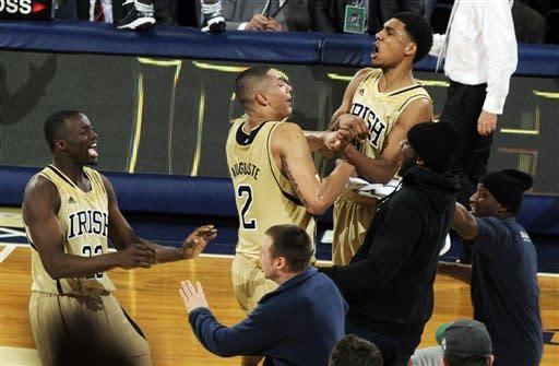 Notre Dame's Jerian Grant, left, Zach Auguste (2) and Cameron Biedscheid celebrate following their 104-101 win against Louisville in the fifth overtime of their NCAA college basketball game, Saturday, Feb. 9, 2013, in South Bend, Ind. (AP Photo/Joe Raymond)