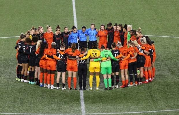 Portland Thorns and Houston Dash players, along with referees, gather at midfield, in demonstration of solidarity with two former NWSL players who came forward with allegations of sexual harassment and misconduct against a prominent coach, during the first half of an NWSL soccer match in Portland, Ore., Wednesday, Oct. 6, 2021. (Steve Dipaola/AP Photo - image credit)