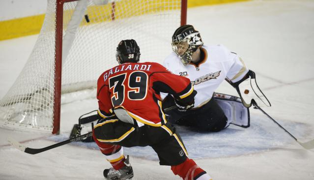 Anaheim Ducks goalie Jonas Hiller, right, from the Czech Republic, lets in a goal from Calgary Flames' TJ Galiardi during the first period of an NHL hockey game in Calgary, Alberta, Wednesday, March 12, 2014. (AP Photo/The Canadian Press, Jeff McIntosh)