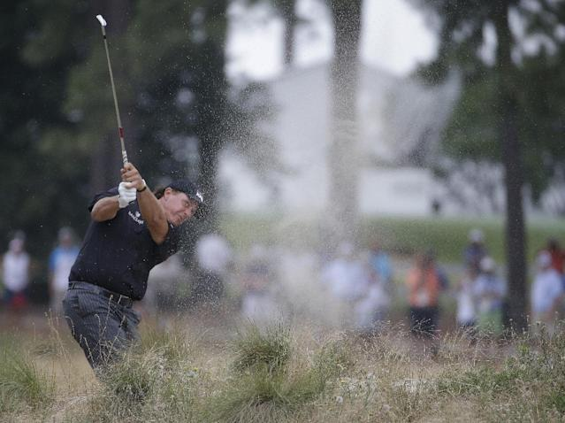 Phil Mickelson hits out of the native area on the fifth hole during the first round of the U.S. Open golf tournament in Pinehurst, N.C., Thursday, June 12, 2014. (AP Photo/David Goldman)
