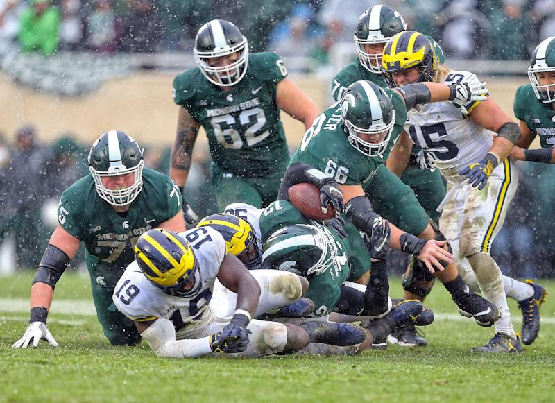 Michigan State Spartans quarterback Rocky Lombardi (12) is sacked by Michigan Wolverines defensive lineman Bryan Mone (90) during the second half of a game at Spartan Stadium.