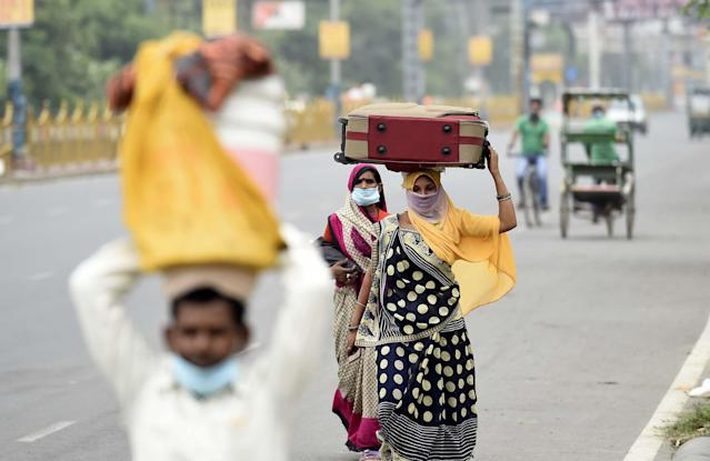 NEW DELHI, INDIA - MAY 13: Migrants leaving with luggage for their home states on foot during lockdown, near Anand Vihar, on May 13, 2020 in New Delhi, India. (Photo by Arvind Yadav/Hindustan Times via Getty Images)