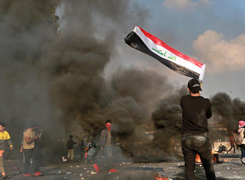A protester waves the national flag during clashes with security forces in central Baghdad, Iraq, Monday, Jan. 20, 2020. Iraqi security forces also used live rounds, wounding over a dozen protesters, medical and security officials said, in continuing violence as anti-government demonstrators make a push to revive their movement in Baghdad and the southern provinces. (AP Photo/Hadi Mizban)