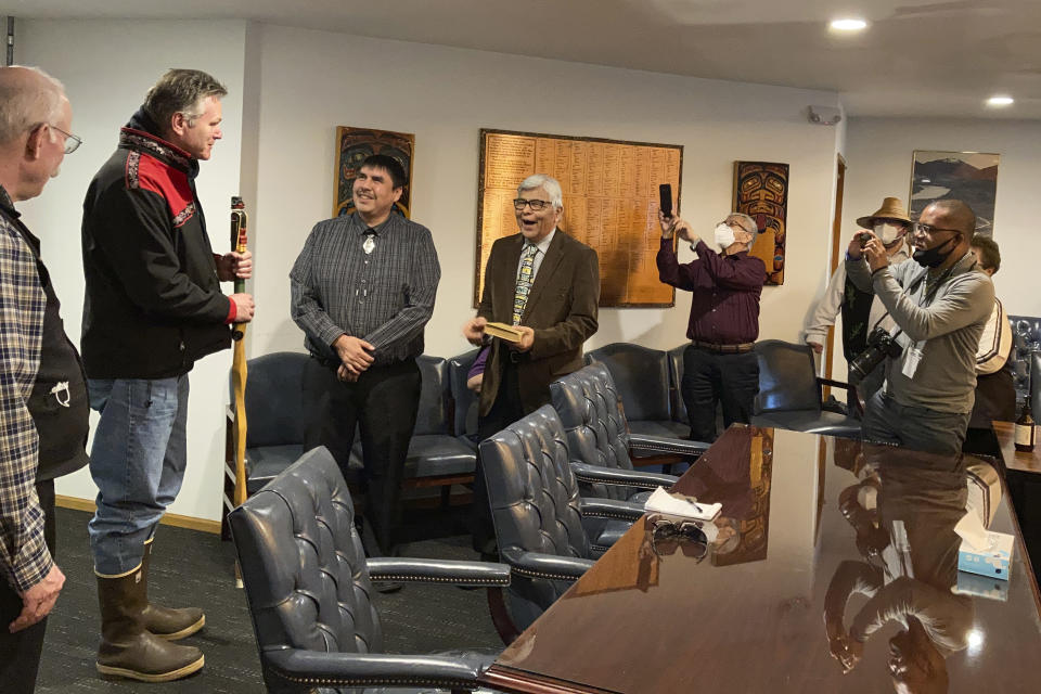 Metlakatla Indian Community Mayor Reginald Atkinson, fourth from left, laughs as he presents gifts to Alaska Gov. Mike Dunleavy on Thursday, April 22, 2021, in Metlakatla, Alaska. Dunleavy is shown second from left, holding a talking stick he was given as a gift. (AP Photo/Becky Bohrer)