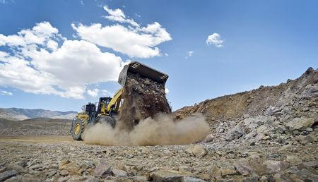 FILE PHOTO: A front-end loader is used to move material inside the open pit at Molycorp's Mountain Pass Rare Earth facility in Mountain Pass, California June 29, 2015. REUTERS/David Becker/File Photo