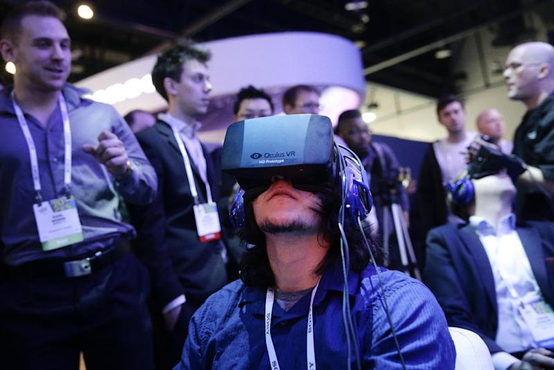 """FILE - In this Jan. 7, 2014 file photo, show attendees play a video game wearing Oculus Rift virtual reality headsets at the Intel booth at the International Consumer Electronics Show(CES), in Las Vegas. Filmmaker Danfung Dennis' latest project: a virtual reality documentary, """"Zero Point,"""" will be the first movie released for the Oculus Rift, a VR headset that provides an immersive 110-degree field of view with high-definition stereoscopic 3D and low-latency head tracking. (AP Photo/Jae C. Hong, File)"""