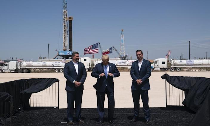 "<span class=""element-image__caption"">Donald Trump adjusts his jacket as he stands with Double Eagle Energy co-CEOs Cody Campbell, left, and John Sellers in Midland, Texas.</span> <span class=""element-image__credit"">Photograph: Evan Vucci/AP</span>"