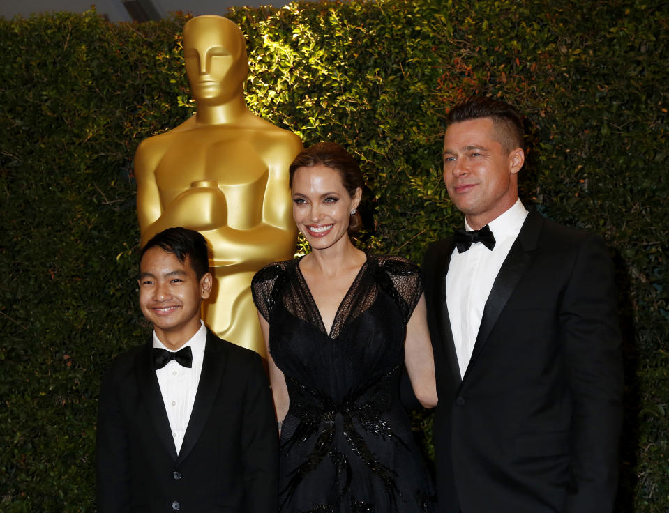 Angelina Jolie and partner Brad Pitt and son Maddox arrive at the 5th Annual Academy of Motion Picture Arts and Sciences Governors Awards in Hollywood November 16, 2013. Jolie is being honored with the Jean Hersholt Humanitarian Award, which is an Oscar statuette at the ceremony. REUTERS/Fred Prouser   (UNITED STATES  - Tags: ENTERTAINMENT)