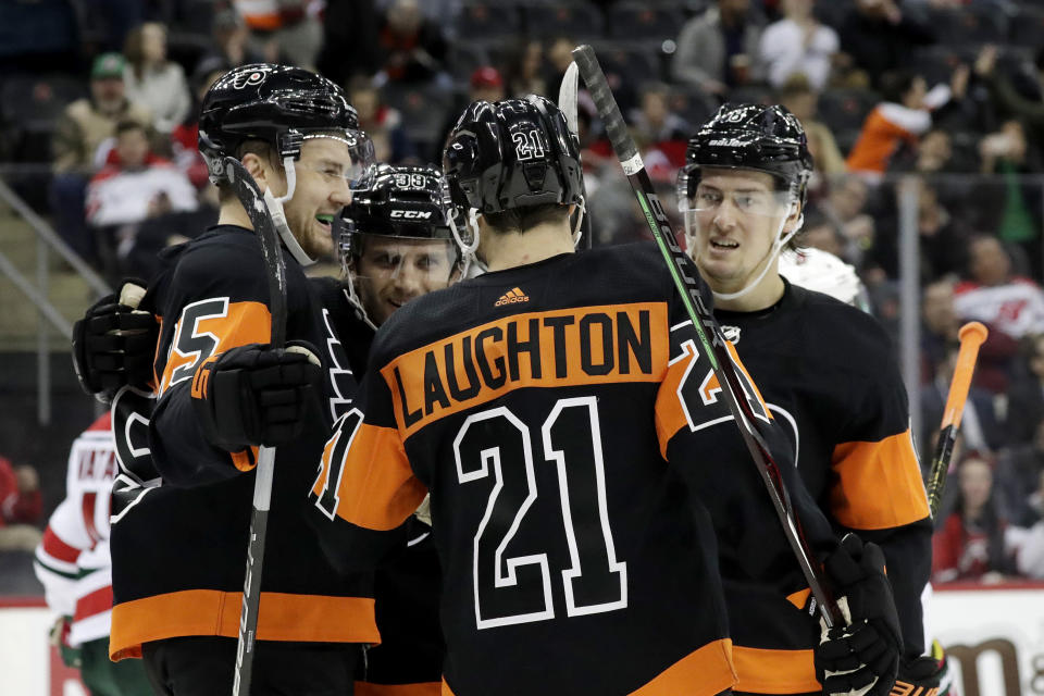 Philadelphia Flyers left wing James van Riemsdyk, far left, celebrates his first-period goal with teammates during the team's NHL hockey game against the New Jersey Devils, Friday, March 1, 2019, in Newark, N.J. (AP Photo/Julio Cortez)