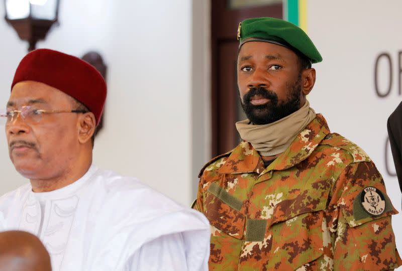 FILE PHOTO: Colonel Assimi Goita, leader of Malian military junta, looks on while he stands behind Niger's President Mahamadou Issoufou during a photo opportunity after the Economic Community of West African States (ECOWAS) consultative meeting in Accra