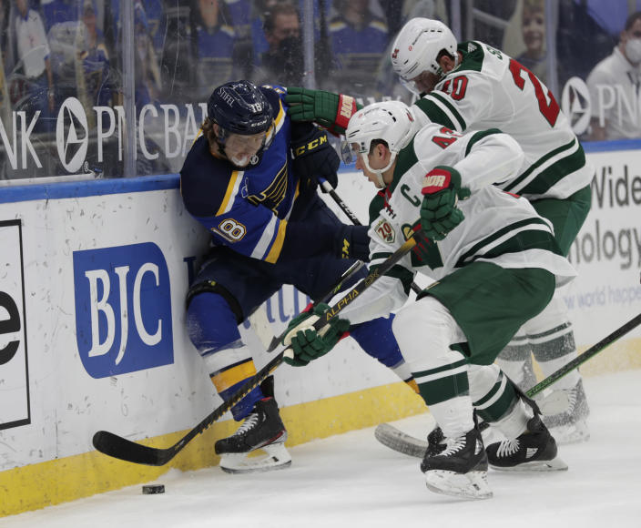 St. Louis Blues' Robert Thomas (18) battles for the loose puck along the boards with Minnesota Wild's Jared Spurgeon (46) and Ryan Suter (20) in the second period of an NHL hockey game, Wednesday, May 12, 2021 in St. Louis. (AP Photo/Tom Gannam)