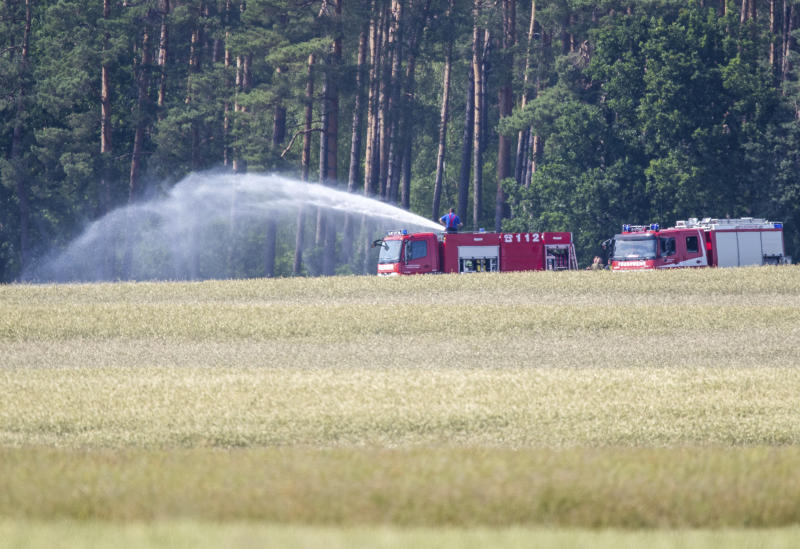 Firefighters work in Nossentiner Huette, eastern Germany on Monday, June 24, 2019 where two German Eurofighter military planes crashed earlier today. (Jens Buettner/dpa via AP)