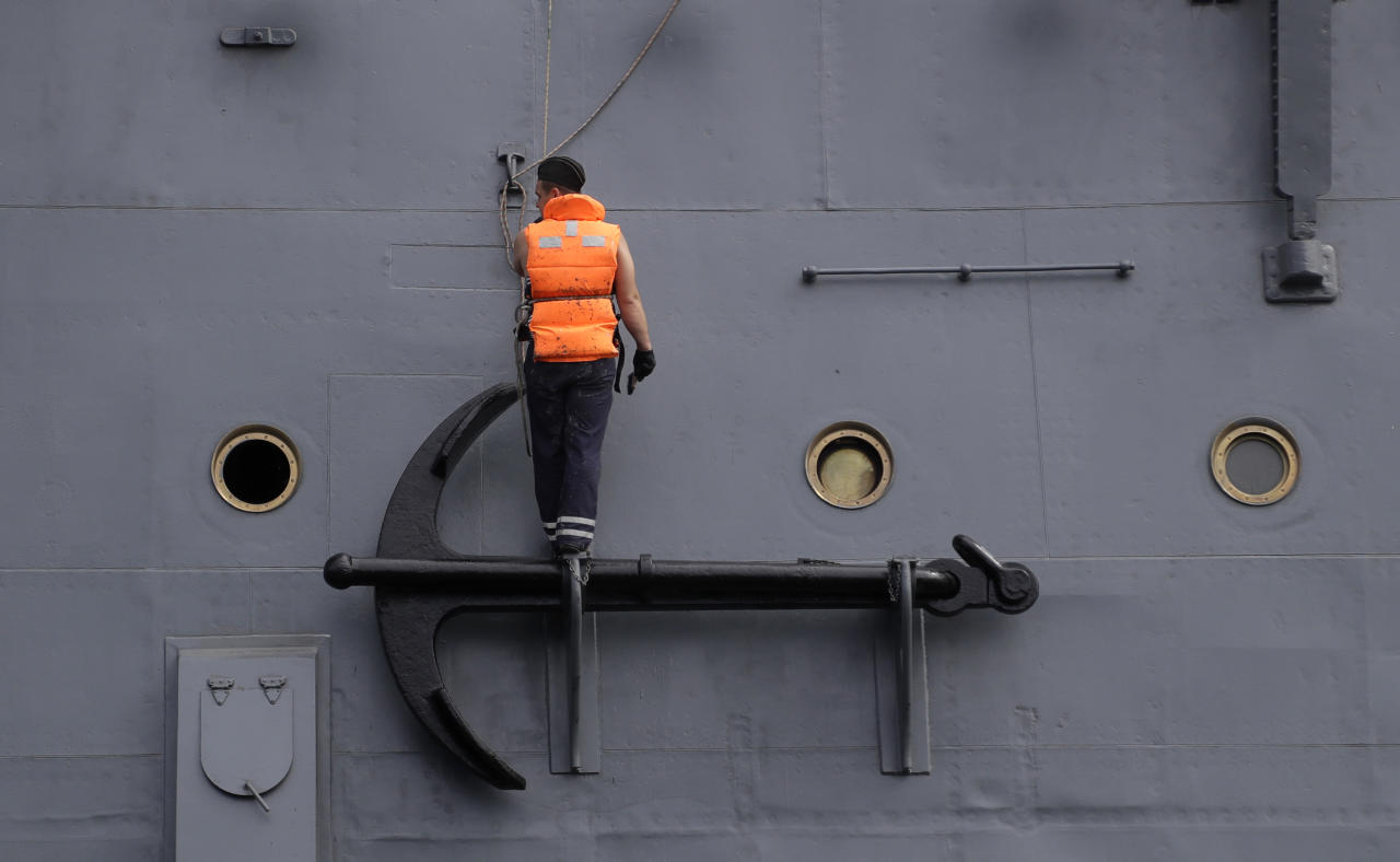 A navy sailor stands on an anchor of the Aurora cruise ship docked at the Neva river during the 2018 soccer World Cup in St. Petersburg, Russia, Friday, July 13, 2018. (AP Photo/Petr David Josek)