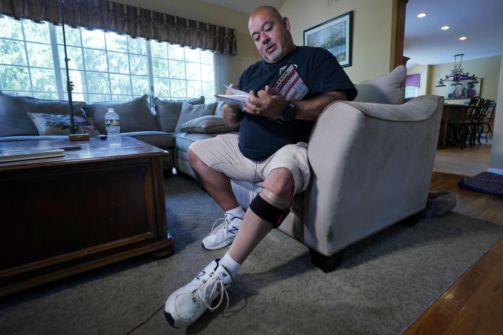 """Will Jimeno, the former Port Authority police officer who was rescued from the rubble of the Sept. 11, 2001 attacks at the World Trade Center, reads from """"Immigrant, American, Survivor,"""" a children's book he wrote that draws on his experience, during an interview in his home, in Chester, N.J., Monday, Aug. 2, 2021. Injured in the attack, Jimeno wears a compression sock and leg brace band on his left leg. (AP Photo/Richard Drew)"""