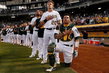 Bruce Maxwell of the Oakland Athletics kneels as teammate Mark Canha places his hand on Maxwell's shoulder during the singing of the national anthem in Oakland. REUTERS/Stephen Lam