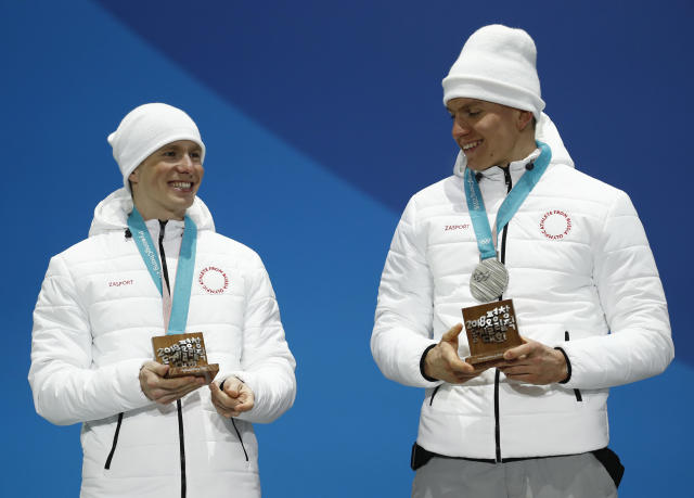 Silver medalists in the men's team sprint freestyle cross-country skiing Russian athletes Denis Spitsov and Alexander Bolshunov, pose during the medals ceremony at the 2018 Winter Olympics in Pyeongchang, South Korea, Thursday, Feb. 22, 2018. (AP Photo/Patrick Semansky)