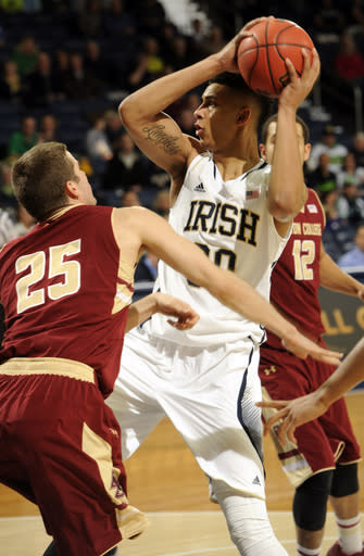 Notre Dame forward Zach Auguste, right, throws a pass around Boston College guard Joe Rahon during the first half of an NCAA college basketball game, Saturday, Feb. 1 2014, in South Bend, Ind. (AP Photo/Joe Raymond)