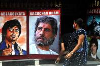 A fan of Bollywood actor Amitabh Bachchan hangs posters of the actor as a woman passes by at the gate of All Bengal Amitabh Bachchan Fan Club in Kolkata on July 12, 2020. - Bollywood megastar Amitabh Bachchan, 77, tested positive for COVID-19 on July 11 and was admitted to hospital in Mumbai, with his actor son Abhishek -- who also announced he had the virus -- saying both cases were mild. (Photo by Dibyangshu SARKAR / AFP)