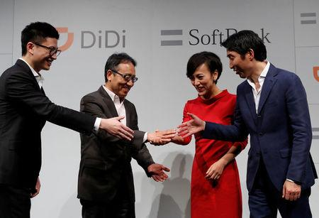 Vice President of Didi Chuxing Stephen Zhu, SoftBank Corp's CEO Ken Miyauchi, President of Didi Chuxing Jean Liu and SoftBank Corp' executive Keigo Sugano shake hands after a news conference about their Japanese taxi-hailing joint venture in Tokyo, Japan, July 19, 2018.  REUTERS/Kim Kyung-Hoon