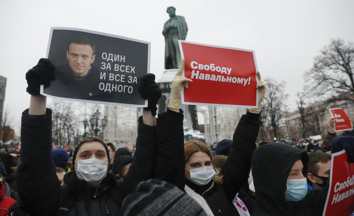 """People gather during a protest against the jailing of opposition leader Alexei Navalny in Pushkin square at the statue of Alexander Pushkin in the background in Moscow, Russia, Saturday, Jan. 23, 2021. Protesters hold posters reading """"Freedom for Navalny!"""" and """"One for all and all for one"""" with Navalny's portrait. Authorities in Russia have taken measures to curb protests planned for Saturday against the jailing of Navalny. (AP Photo/Pavel Golovkin)"""