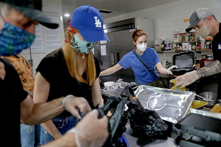 """Volunteers prep meals for homeless people and other clients of the Hollywood Food Coalition. <span class=""""copyright"""">(Gary Coronado / Los Angeles Times)</span>"""
