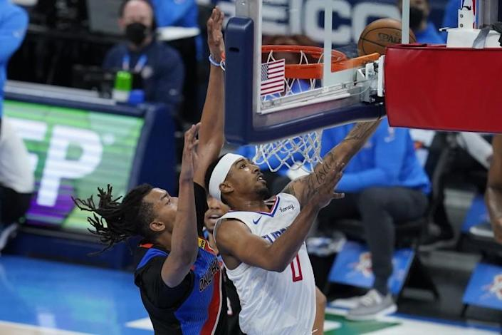 Los Angeles Clippers guard Jay Scrubb (0) shoots in front of Oklahoma City Thunder center Moses Brown, left, in the second half of an NBA basketball game Sunday, May 16, 2021, in Oklahoma City. (AP Photo/Sue Ogrocki)