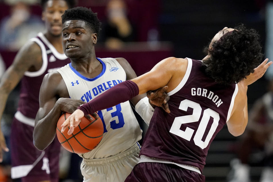 New Orleans guard Kmani Doughty (13) tries to get by Texas A&M guard Andre Gordon (20) during the first half of an NCAA college basketball game Sunday, Nov. 29, 2020, in College Station, Texas. (AP Photo/Sam Craft)