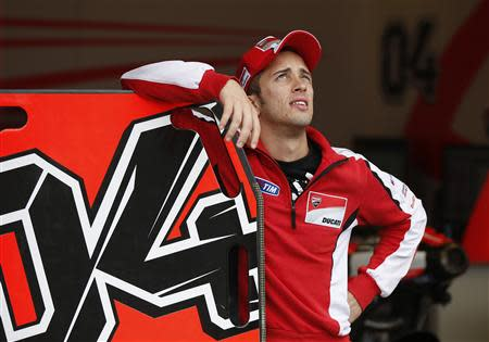 Ducati MotoGP rider Andrea Dovizioso of Italy looks up into the sky from his team's garage ahead of Sunday's Japanese Grand Prix in Motegi, north of Tokyo October 25, 2013. REUTERS/Toru Hanai